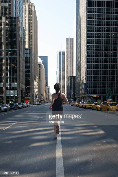 Rear view of woman jogging down Avenue of Americas (6th Avenue), Manhattan, New York, America, USA