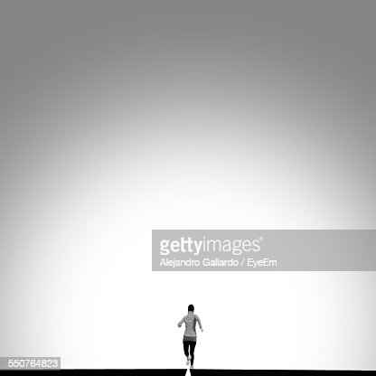 Rear View Of Woman Jogging On Road