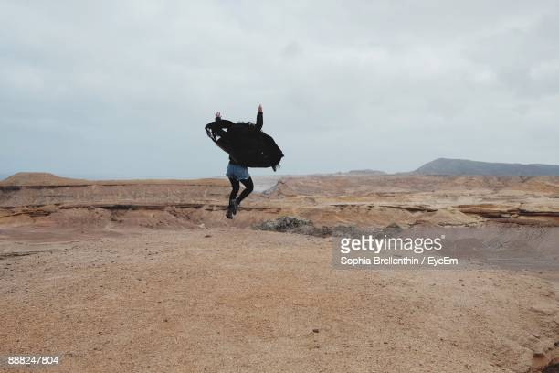 Rear View Of Woman Jumping On Sand At Desert
