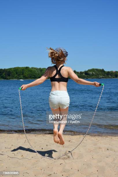 Rear View Of Woman Jumping Rope At Sandy Beach Against Clear Blue Sky