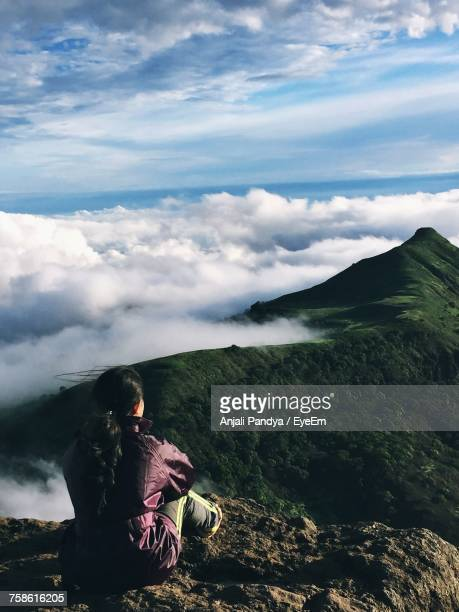 Rear View Of Woman Looking At View While Sitting On Mountain Against Cloudy Sky
