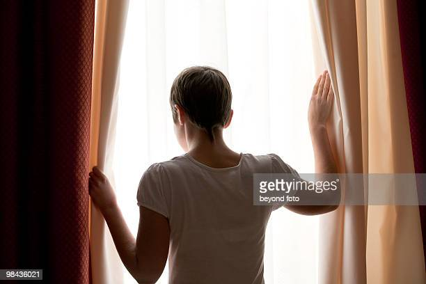 rear view of woman looking out of window