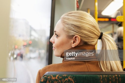 Rear view of woman looking out through bus window