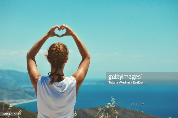 Rear View Of Woman Making Heart Shape With Hands Against Sea