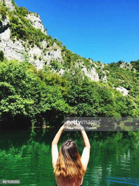 Rear View Of Woman Making Heart Shape With Hands By Una River Against Mountain