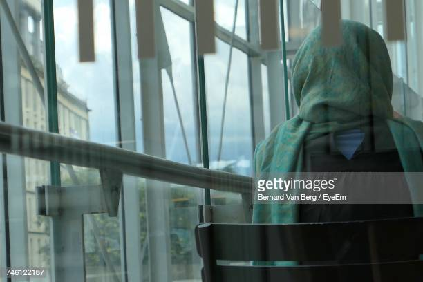 Rear View Of Woman On Chair Seen Through Glass At Railroad Station