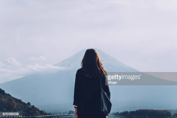 Rear view of woman overlooking at Mount Fuji against clear sky