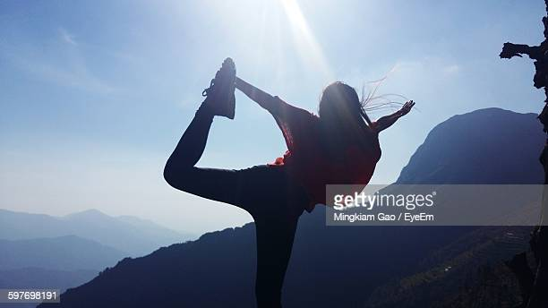 Rear View Of Woman Performing Yoga On Mountain Against Sky