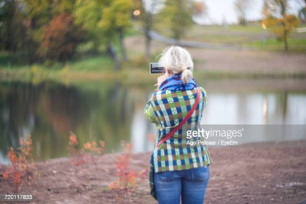 Rear View Of Woman Photographing Lake In Mobile Phone