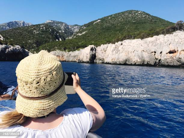 Rear View Of Woman Photographing Mountains From Boat In Sea