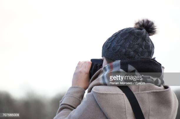 Rear View Of Woman Photographing While Standing Against Sky