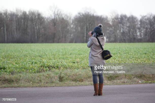 Rear View Of Woman Photographing While Standing On Road By Field