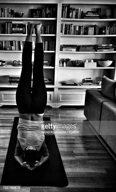 Rear View Of Woman Practicing Headstand Yoga On Mat At Home