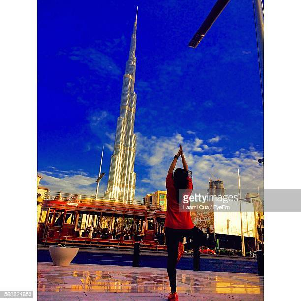 Rear View Of Woman Practicing Yoga In Front Of Burj Khalifa Against Blue Sky