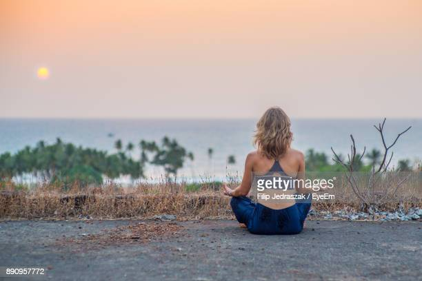 Rear View Of Woman Practicing Yoga On Footpath Against Sea During Sunset