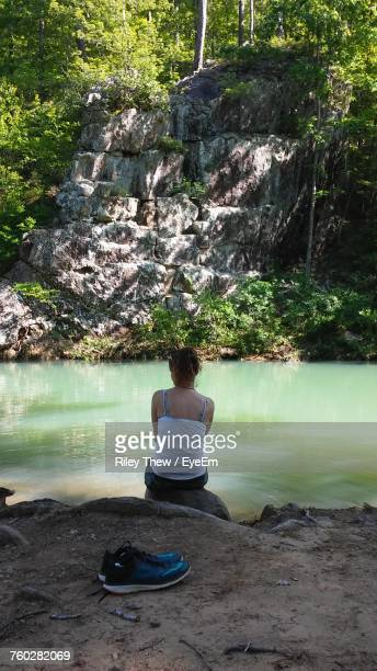 Rear View Of Woman Relaxing On Rock By River