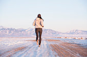 Rear view of woman running in winter landscape, Colorado, USA