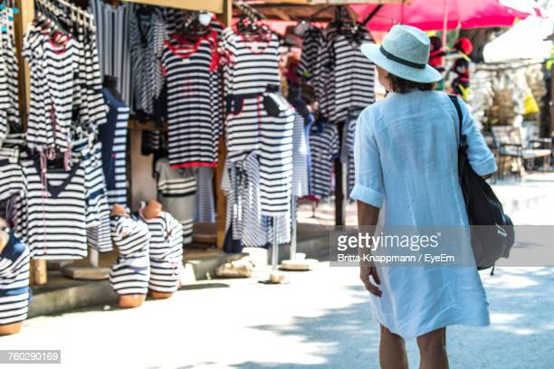 Rear View Of Woman Shopping On Street At Market Stall