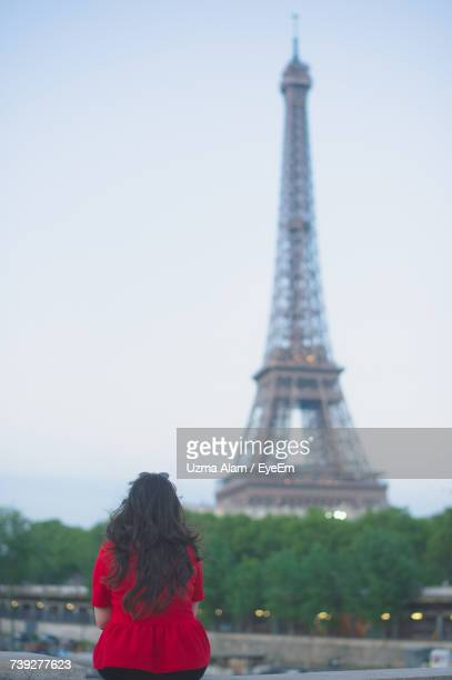 Rear View Of Woman Sitting Against Eiffel Tower