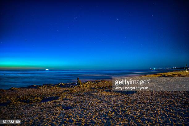 Rear View Of Woman Sitting At Beach During Night