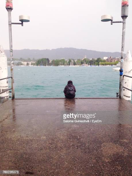 Rear View Of Woman Sitting At Jetty By Sea