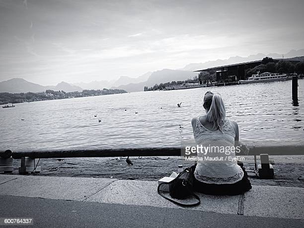 Rear View Of Woman Sitting At Lakeshore Against Cloudy Sky