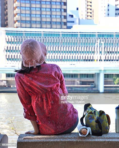 Rear View Of Woman Sitting By River Against Building