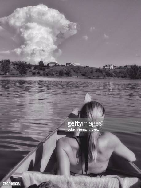 Rear View Of Woman Sitting In Boat Over River Against Sky During Sunny Day