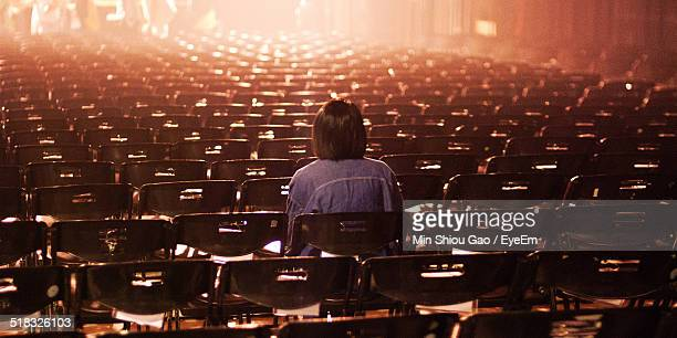 Rear View Of Woman Sitting In Empty Theater