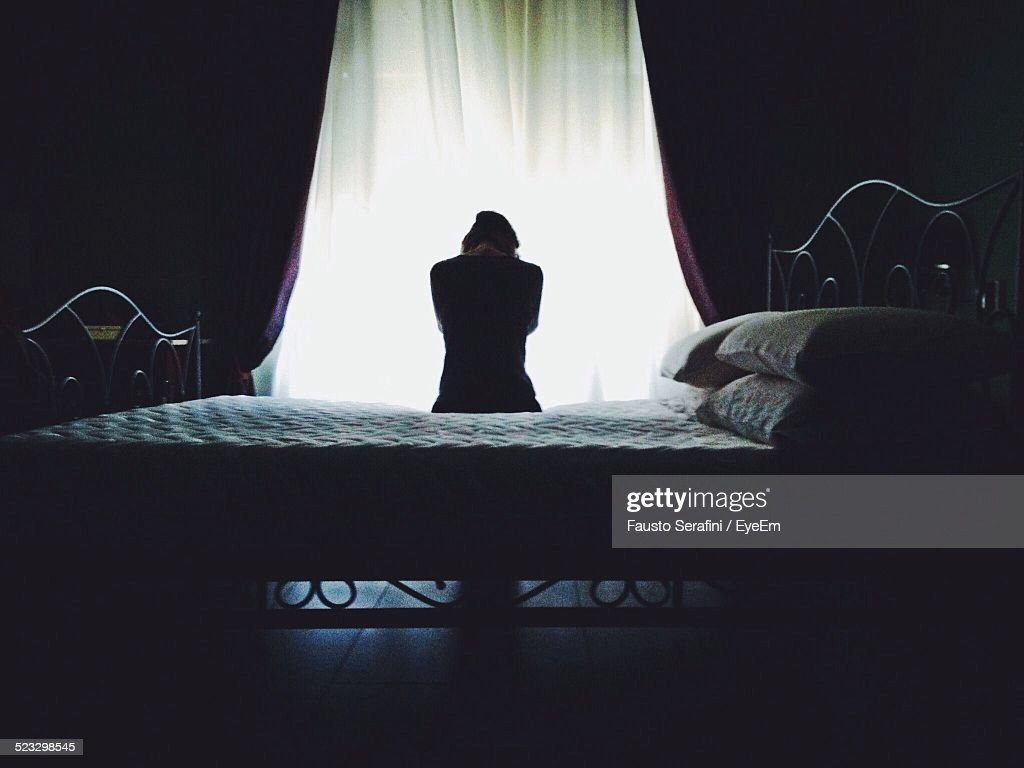 Rear View Of Woman Sitting On Bed Against Curtain : Stock Photo