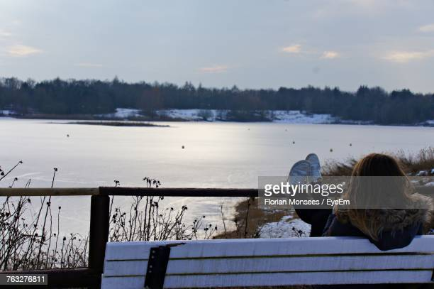 Rear View Of Woman Sitting On Bench Against Lake During Winter