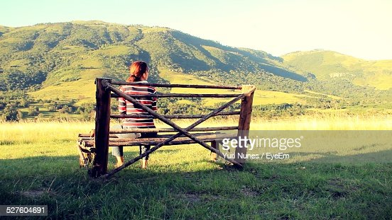Rear View Of Woman Sitting On Bench Against Mountains
