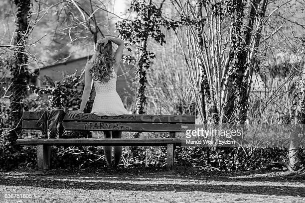 Rear View Of Woman Sitting On Bench At Field