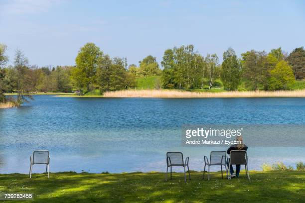 Rear View Of Woman Sitting On Chair At Lakeshore