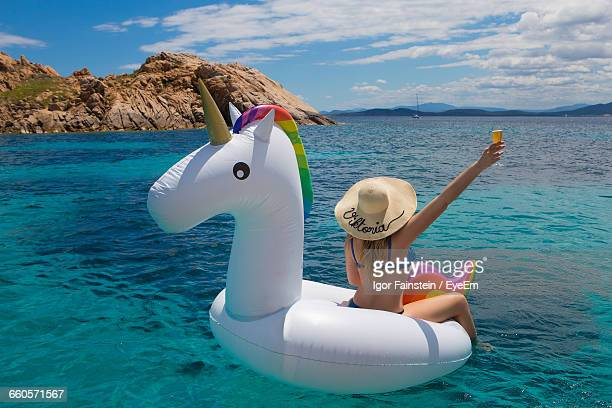 Rear View Of Woman Sitting On Inflatable Unicorn In Aegean Sea Against Sky