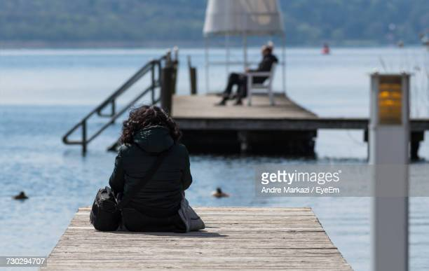 Rear View Of Woman Sitting On Jetty Over Lake Against Sky