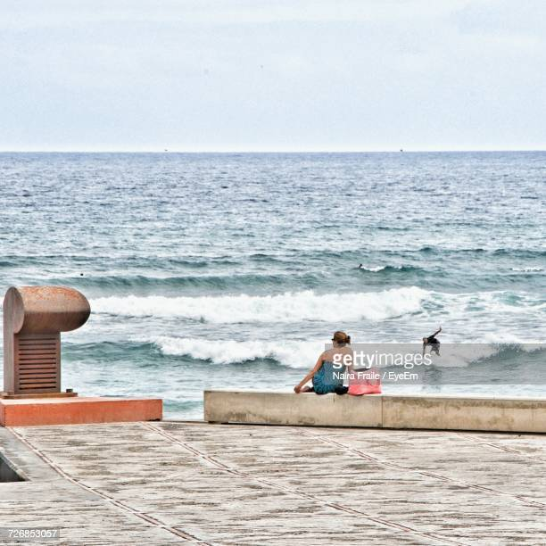 Rear View Of Woman Sitting On Retaining Wall While Man Surfboarding In Sea