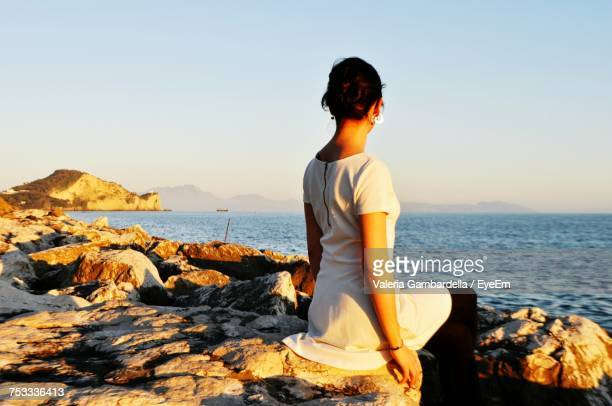 Rear View Of Woman Sitting On Rock At Beach During Sunset