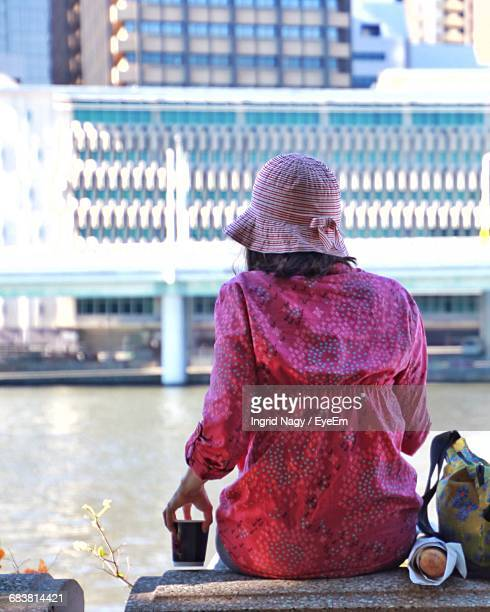 Rear View Of Woman Sitting While Holding Coffee By River Against Building