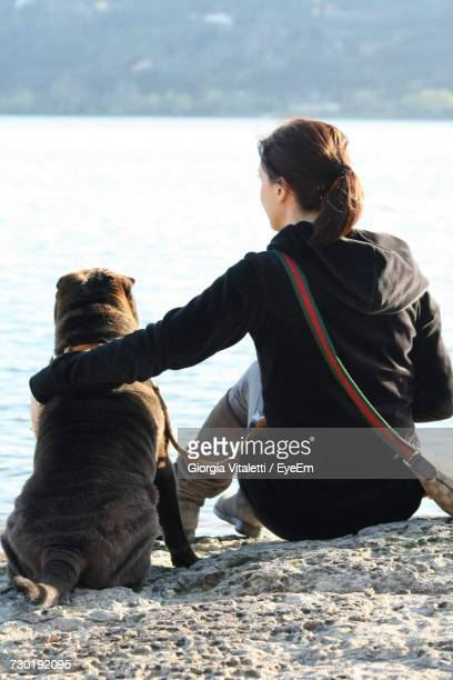 Rear View Of Woman Sitting With Dog On Rock Formation While Looking At River
