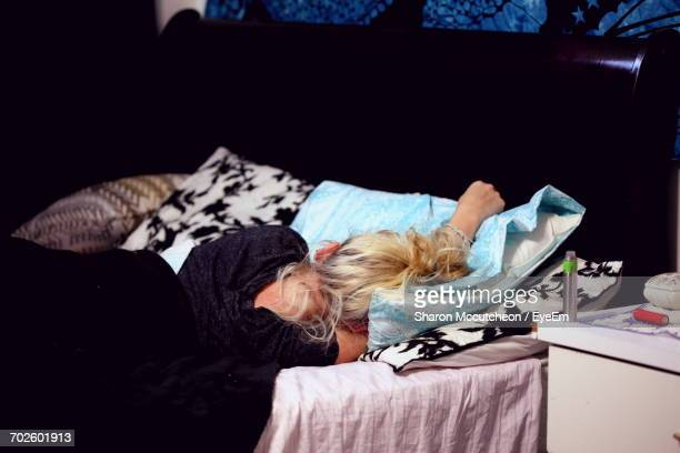 Rear View Of Woman Sleeping On Bed