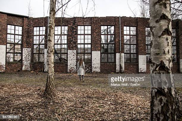 Rear View Of Woman Standing Against Abandoned Building