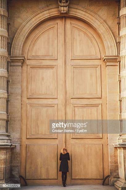 Rear View Of Woman Standing Against Closed Wooden Door Of Historic Building