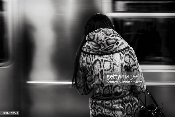 Rear View Of Woman Standing Against Train At Station