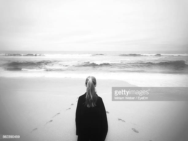 Rear View Of Woman Standing At Beach Against Clear Sky