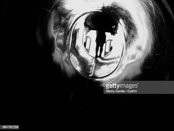 Rear View Of Woman Standing At End Of Tunnel