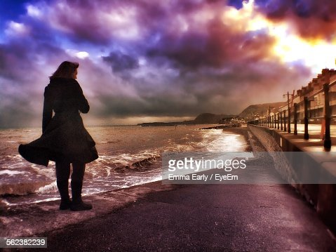 Rear View Of Woman Standing At Shore Against Cloudy Sky