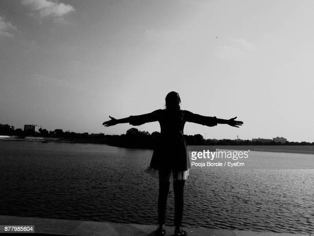 Rear View Of Woman Standing By Lake Against Clear Sky