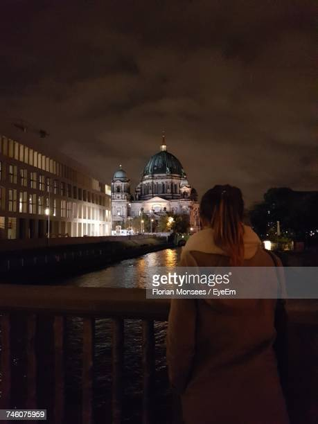 Rear View Of Woman Standing By Railing Against Berlin Cathedral At Night