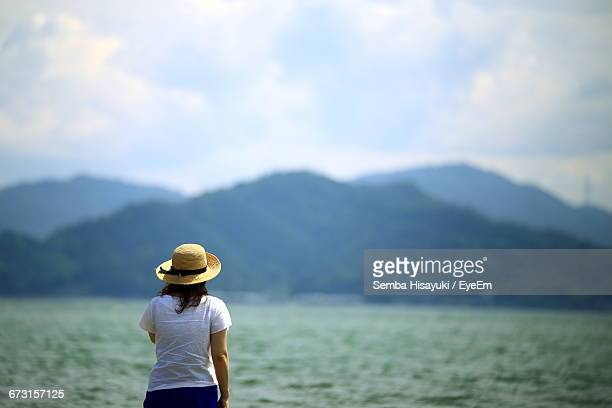 Rear View Of Woman Standing By River Against Sky